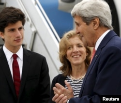 U.S. Ambassador to Japan Caroline Kennedy, center, and her son Jack Schlossberg, left, greet Secretary of State John Kerry as he arrives, ahead of G-7 foreign minister meetings, at Marine Corps Air Station Iwakuni, Japan, April 10, 2016.