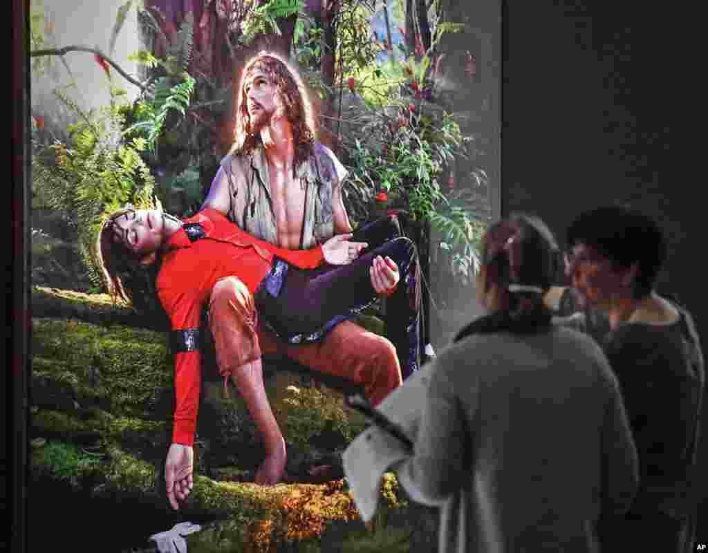 بینندگان از مقابل تابلوی موسوم به مسیح آمریکایی می گذرند که دیوید لاچاپل آن را کشیده و مایکل جکسون را در روی پای مسیح نشان می دهد. این نقاشی روی دیوار یک موزه در بن آلمان به نمایش گذاشته شده است.