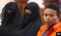 Terdakwa pembuat bom panci, Dian Yulia Novi, tengah, diapit oleh suaminya Nur Solihin, kanan, dan perekrutnya Tutin dalam persidangan di Pengadilan Jakarta Timur, 23 Agustus 2017.