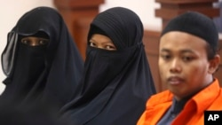 Indonesian militant Dian Yulia Novi, center, is flanked by her husband Nur Solihin, right, and her recruiter Tutin as they sit on the defendant's bench during their trial hearing at East Jakarta District Court in Jakarta, Indonesia, Wednesday, Aug. 23, 2017.