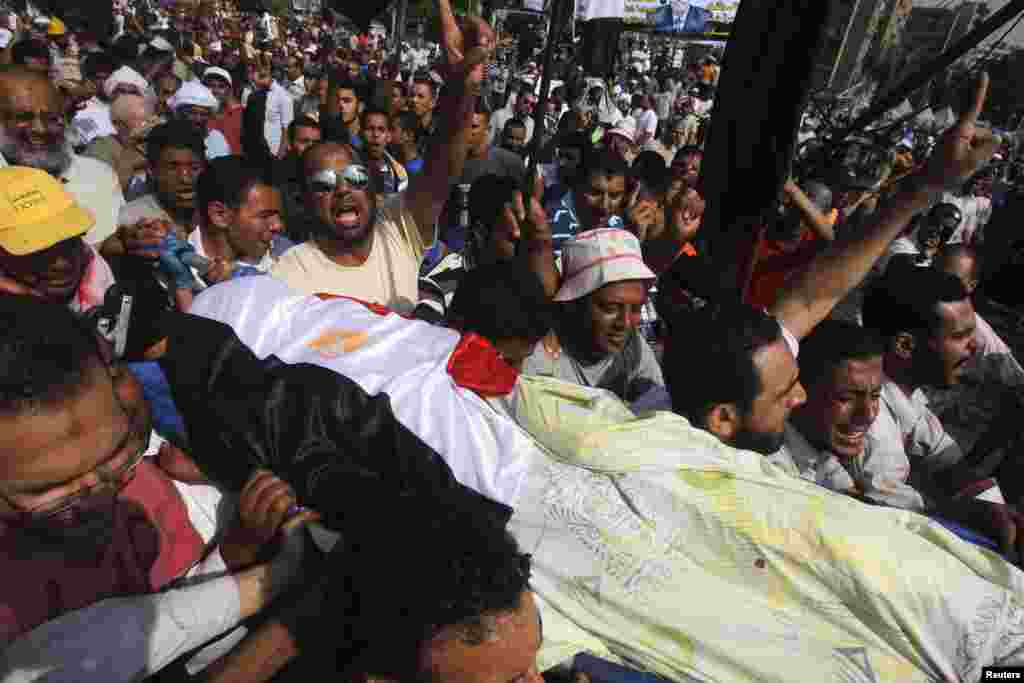 Supporters of Egypt's deposed President Mohamed Morsi carry the body of a fellow supporter killed outside the Republican Guard headquarters in Cairo, July 8, 2013.