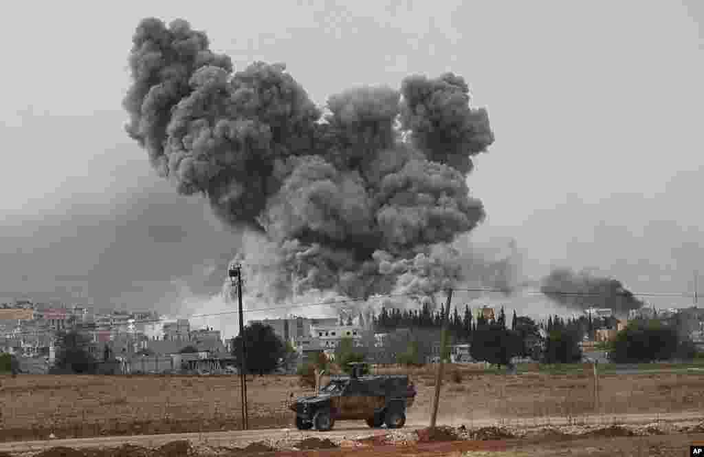 Epaisse fumée et débris s'élèvent après une frappe de la coalition menée oar les Etats-Unis à Kobani, en Syrie, dimanche le 12 ocotbre 2014. (AP Photo/Lefteris Pitarakis)