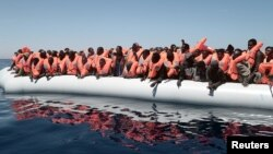 FILE - A plastic raft overcrowded with migrants drifts in the central Mediterranean Sea, May 18, 2017. More than 2,000 migrants were rescued overnight Friday.