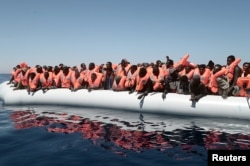 FILE - A plastic raft overcrowded with migrants drifts in the central Mediterranean Sea, May 18, 2017.