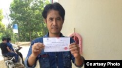 Chhoun Chheng shows his registration slip after authority in Pailin province allowed him to register there. Chheng was refused twice before at two other provinces.