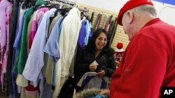 In this 2012 file photo, a shopper looking for clothes at the Salvation Army store in Staten Island, New York, receives a surprise $100 donation.