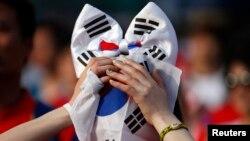 Một fan bóng đá che mặt với lá cờ Nam Triều Tiên sau khi đội này bị loại khỏi World Cup, 27/6/14