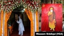 کراچی کے ایک گورو دوارے کے باہر لگی بابا گورونانک کی تصویر اور ایک عقیدت متد