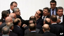 Turkish legislators from Prime Minister Recep Tayyip Erdogan's ruling party and the main opposition Republican People's Party brawl during a tense all-night debate over a controversial law on changes to a council that appoints and oversees judges and prosecutors, in Ankara, Feb. 15, 2014.