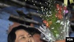 Tokoh oposisi Birma, Aung San Suu Kyi, menerima karangan bunga dari seorang pendukungnya setelah bebas dari tahanan rumah akhir pekan ini.