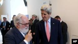 Menteri Luar Negeri John Kerry (kanan) berbincang dengan Komisioner Iklim Uni Eropa Miguel Arias Canete di Wina, Austria (22/7). (AP/Ronald Zak)