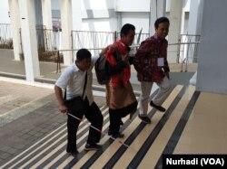 Wildan (tengah) dipandu Arif Maftuhin, Direktur Pusat Layanan Difabel UIN Sunan Kalijaga mengakses area yang belum diakrabinya di kampus. (Foto: VOA/ Nurhadi))