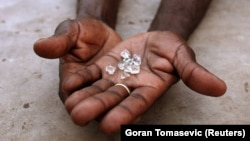 FILE PHOTO: An illegal diamond dealer from Zimbabwe displays diamonds for sale in Manica, near the border with Zimbabwe, September 19, 2010. REUTERS/Goran Tomasevic/File Photo - RC19CE366E30