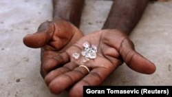 FILE PHOTO: An illegal diamond dealer from Zimbabwe displays diamonds for sale in Manica, near the border with Zimbabwe, September 19, 2010. REUTERS/Goran Tomasevic/File Photo