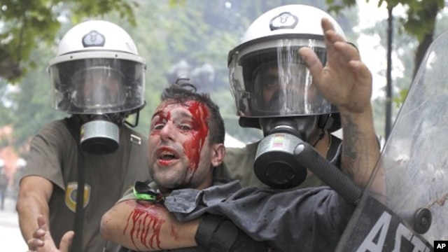 Riot police detain a demonstrator during a protest in Athens' Syntagma (Constitution) square, June 29, 2011.