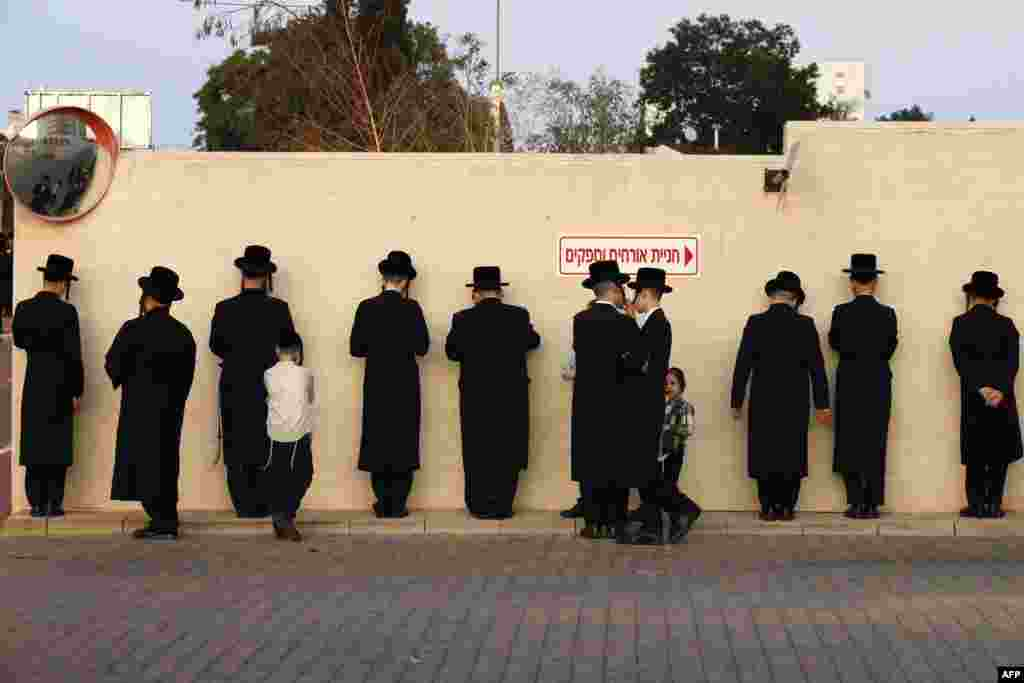 Ultra-Orthodox Jewish men pray along a wall in the Israeli city of Ramat Gan, near Tel Aviv.