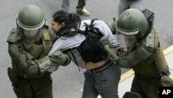 图为一名智利学生8月4日遭到防暴警察逮捕