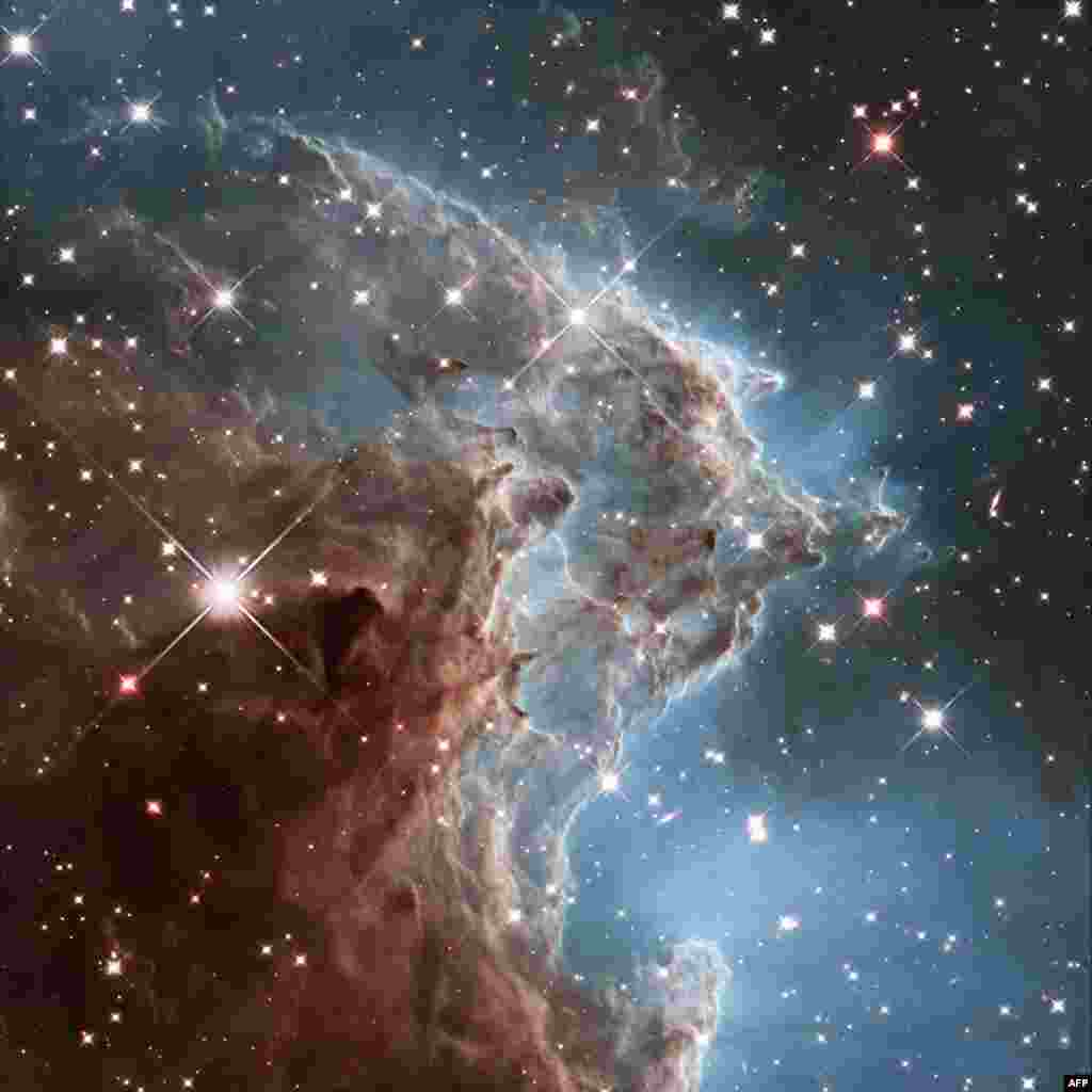 This handout image by the ESA and taken by the NASA/ESA Hubble Space Telescope shows the Monkey Head Nebula or NGC2174, to celebrates its 24th year in orbit. NGC 2174 lies about 6400 light-years away in the constellation of Orion (The Hunter). Hubble prepreviously viewed this part of the sky back in 2011 — the colourful region is filled with young stars embedded within bright wisps of cosmic gas and dust. This portion of the Monkey Head Nebula was imaged in the infrared using Hubble's Wide Field Camera 3.
