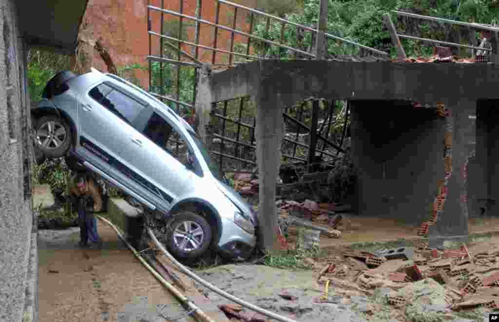 Um homem passa sob um carro danificado pelas enxurradas e deslizamentos em Teresópolis.