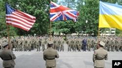 Binh sĩ quân đội Ba Lan cầm cờ của một số quốc gia tham gia cuộc tập trận Anaconda-16 trong lễ khai mạc ở Warsaw, Ba Lan, ngày 6 tháng 6 năm 2016.