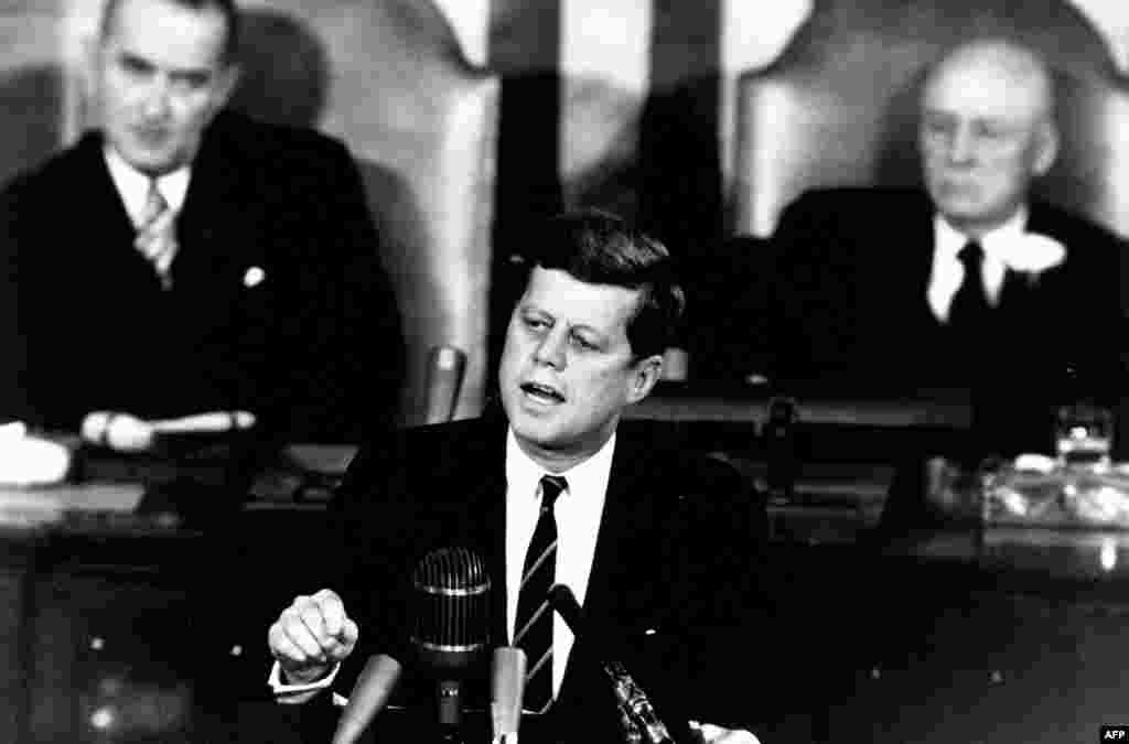 """Trong bài diễn văn lịch sử trước Quốc hội ngày 25 tháng 5, 1961, Tổng thống John F. Kennedy tuyên bố: """"Tôi tin quốc gia này cần cam kết hoàn thành mục tiêu, trước khi thập niên này chấm dứt, đưa người đổ bộ mặt trăng và trở về trái đất an toàn."""" Phía sau"""