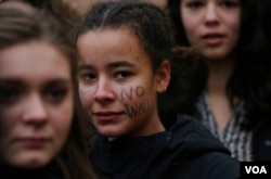 """Ella Thomas, of Brooklyn, N.Y., has """"no wall"""" printed on her face at a rally protesting President Donald Trump's executive orders affecting immigrants, Feb. 7, 2017. (AP/Bebeto Matthews)"""