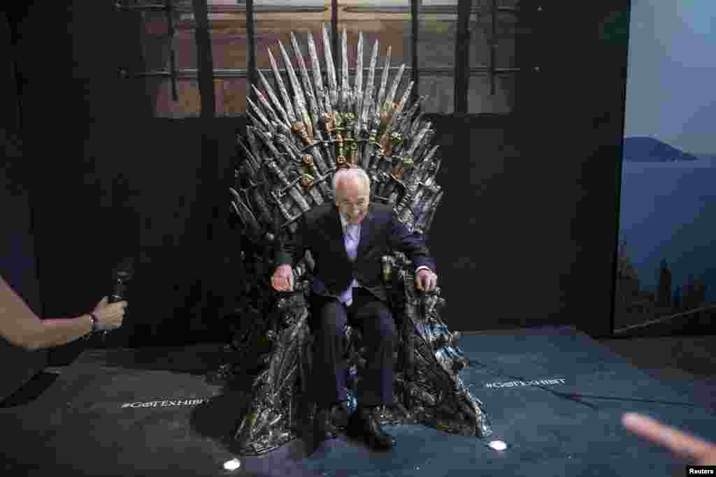 Former Israeli president Shimon Peres smiles as he sits on the Iron Throne during the opening of the Game of Thrones exhibition in Tel Aviv.