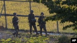South Korean army soldiers patrol the wire fences near the demilitarized zone between the two Koreas in Paju, South Korea, Oct. 7, 2014.