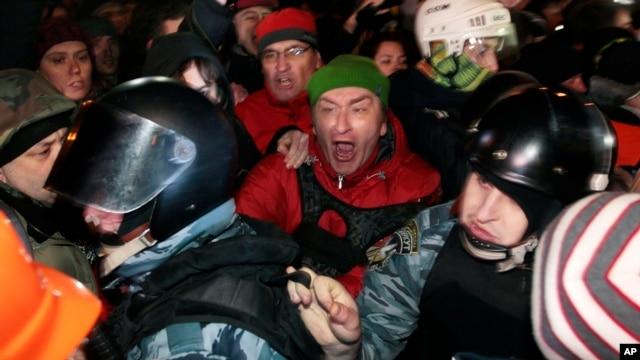 Pro-European Union activists block riot police near a Svyatoshin police station in Kyiv, Ukraine, Saturday, Jan. 11, 2014.