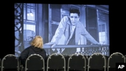 "A woman watches the Elvis Presley film ""King Creole"" in a theater in the ""Elvis Presley's Memphis"" complex Thursday, March 2, 2017, in Memphis, Tenn. (AP Photo/Mark Humphrey)"