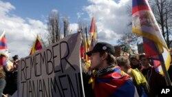 活动人士在捷克共和国首都布拉格挥舞旗帜与自由西藏的旗子参加抗议中国国家主席习近平访问布拉格的集会 (2016年3月29日)
