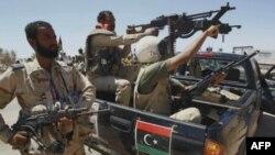 Бойцы ПНС. На багажнике их автомобиля - изображение флага Ливии, который был государственным до прихода к власти Муаммара Каддафи.