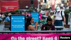 រូបឯកសារ៖ ស្ត្រីម្នាក់ដែលបានពាក់ម៉ាស់ការពារការឆ្លងជំងឺកូវីដ១៩ កំពុងផឹកកាហ្វេនៅតំបន់ទីប្រជុំជន Times Square នៅទីក្រុងញូវយ៉ក រដ្ឋញូវយ៉ក សហរដ្ឋអាមេរិក កាលពីថ្ងៃទី ៥ ខែកក្កដា ឆ្នាំ ២០២០។