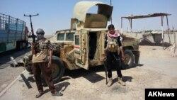 Militantes del grupo Estado islámico junto a un Humvee capturado al ejército iraquí.