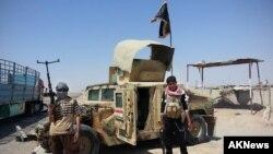 Militantes del Estado islámico junto a un vehículo militar iraqui capturado.