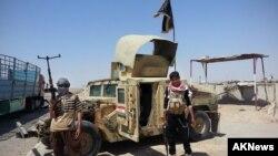 Các chiến binh Nhà nước Hồi giáo đứng cạnh một chiếc Humvee chiếm được bên ngoài trạm kiểm soát của máy lọc dầu Beiji, khoảng 250 km (155 dặm) phía bắc Baghdad, Iraq. (Ảnh chụp ngày 19/6/2014).