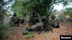 A soldier serving with the African Union Mission in Somalia takes up a defensive position in a fire fight during their joint AMISOM and Somali National Army (SNA) operation to seize and liberate territory from al-Shabab militants in Deyniile, Somalia, May