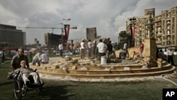 In this Sunday, Nov. 17, 2013 photo, Egyptian municipality laborers work on a memorial base two days before the commemoration of deadly clashes with security forces in 2011, in Tahrir Square, Cairo.