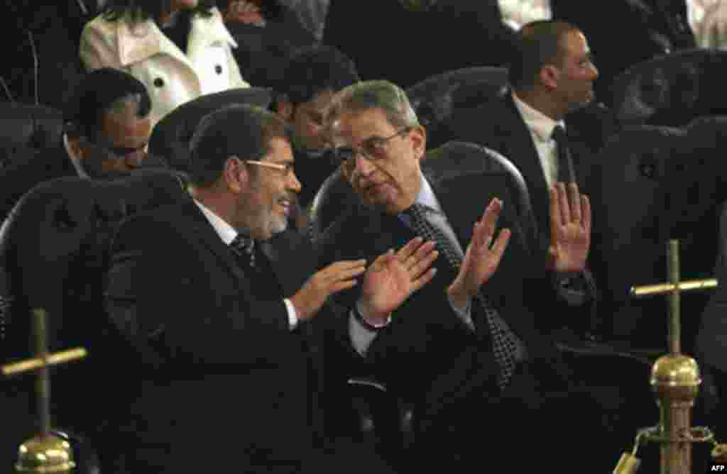 Mohamed Morsi, left, of Egypt's Muslim Brotherhood and Egyptian presidential hopeful Amr Moussa, right, talk before Christmas Eve mass, led by Coptic Pope Shenouda III at the Coptic cathedral in Cairo, Egypt, Friday, Jan. 6, 2012. This is the first Christ