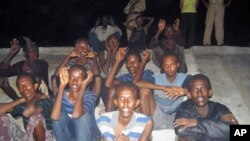 Suspected Somali pirates that arrived on the coast of Dwarka by boat sit on the ground as they are guarded by marine reserve police in Jamnagar district in Gujarat state, June 26, 2011