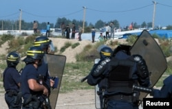 """FILE - French riot police stand guard at the entrance to the """"Jungle"""" as dozens of migrants try to storm trucks that are heading toward the ferry terminal in Calais, France, Sept. 21, 2016."""