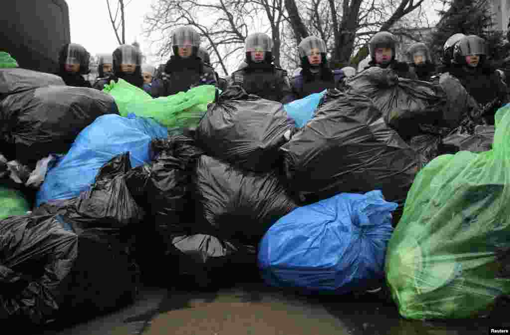 A pile of garbage bags left by pro-European integration protesters lies in front of riot police officers in Kyiv, Ukraine, Dec. 20, 2013.