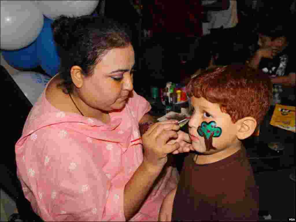 'کراچی کڈز ایکسپو' میں ایک بچہ اپنے چہرے پر فیس پینٹنگ بنوا رہا ہے
