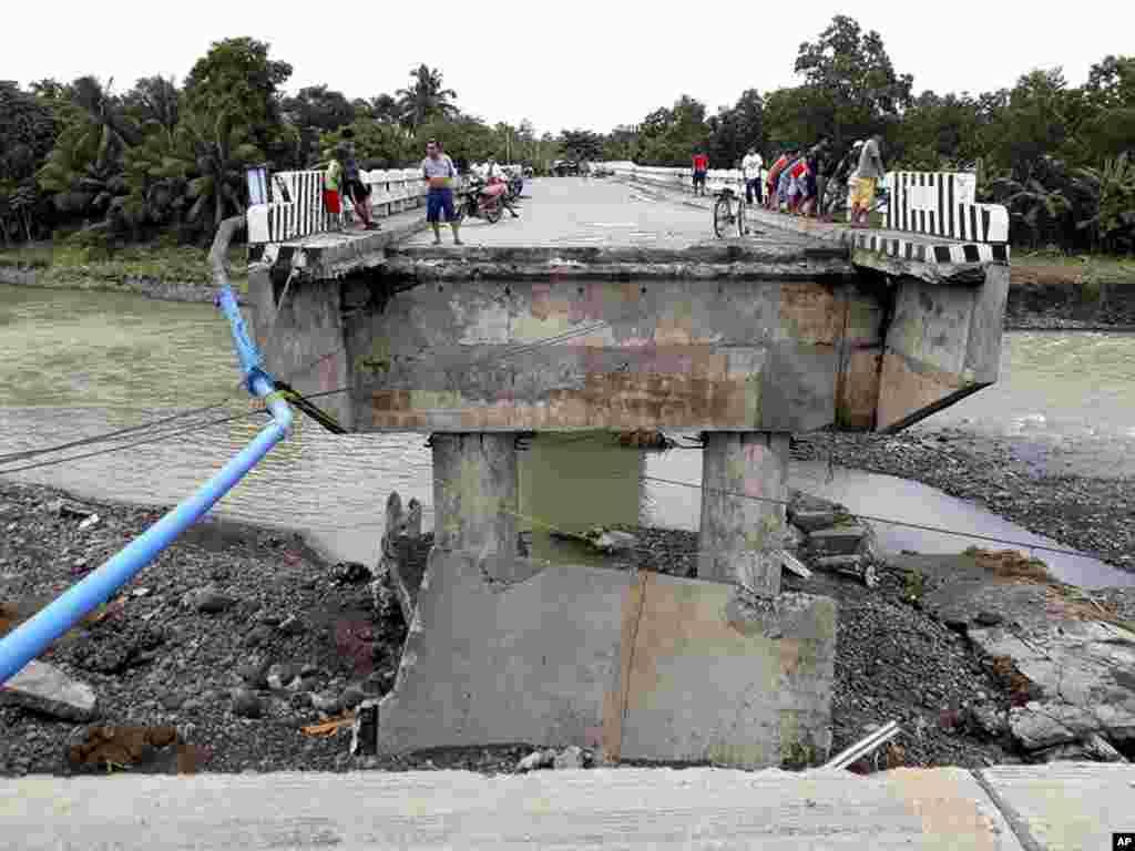 Des gens rassemblés sur un pont détruit par l'inondation provoquée par la tempête tropicale Tembin, le 24 décembre 2017 aux Philippines.