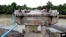 Warga berkumpul di jembatan yang dirusak oleh banjir yang disebabkan oleh badai tropis Tembin, 24 Desember 2017, di Zamboanga Del Sur di Filipina selatan.