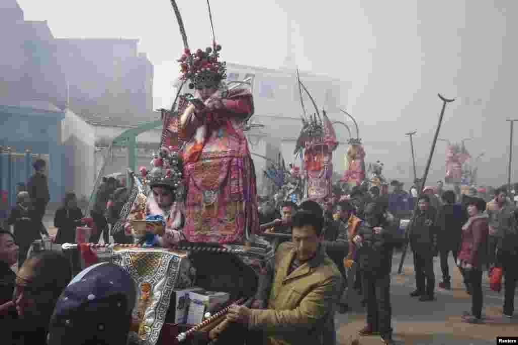 کودکان در حال بازی با تلیفون های خود در یک جشن محلی در ولایت ژجیانگ چین که در آن لباس سنتی پوشیده اند.