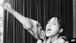 FILE - A young woman calls out to embolden her fellow Red Guards in Beijing's Tiananmen Square at the start of the 1966-76 Cultural Revolution, Aug. 10, 1966.