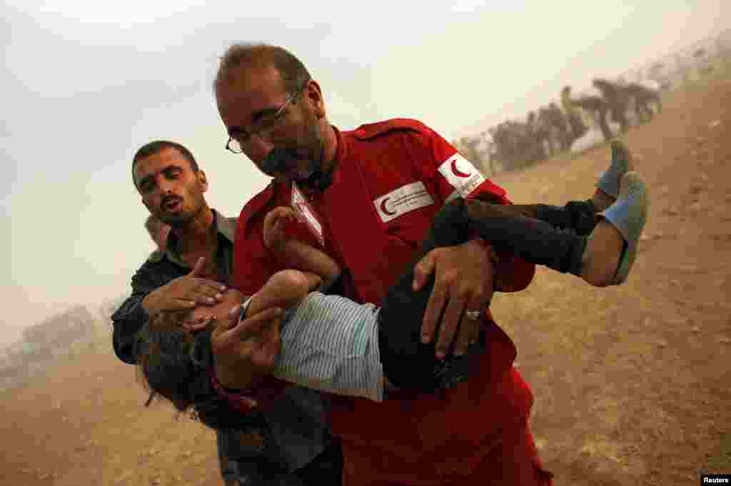 A member of the Syrian Arab Red Crescent carries a Kurdish Syrian refugee girl to the first aid tent after crossing the Turkish-Syrian border near the southeastern town of Suruc in Sanliurfa province, Sept. 25, 2014.