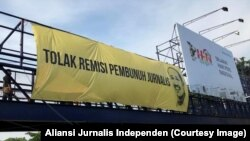 Pemasangan spanduk raksasa menuntut pencabutan remisi pembunuh jurnalis di jembatan penyeberangan depan kantor Jawa Pos di Surabaya, 9 Februari 2019. (Foto: Aliansi Jurnalis Independen)