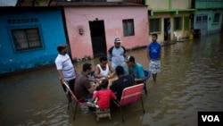 Gente jugando al dominó en las calles inundadas de Higuerote, en Venezuela.